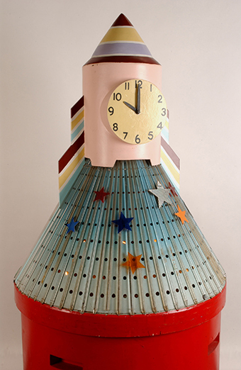 A large clock in the shape of a rocket with a red cylindrical wooden base with a light blue perforated metal skirt covered in vertical plastic rods, a light pink wooden trunk and painted striped cone top.