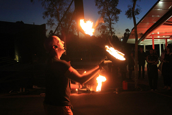 A man juggling fire sticks.
