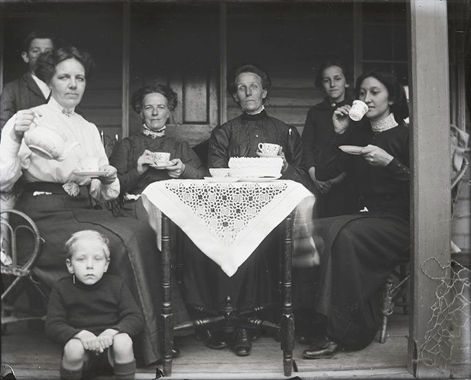 Group portrait of seven people posing on a veranda. Four women sit at a small wooden table. The women hold teacups and the woman at far left is also holding a teapot. At the foot of the table, sitting on the edge of the verandah is a young boy. Another young boy and a young girl stand behind the women at the table. On the table is a lace tablecloth, a teacup and a cake.