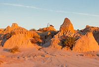 colour photo of ochre-coloured landscape at sunset or sunrise with a variety of outcrops
