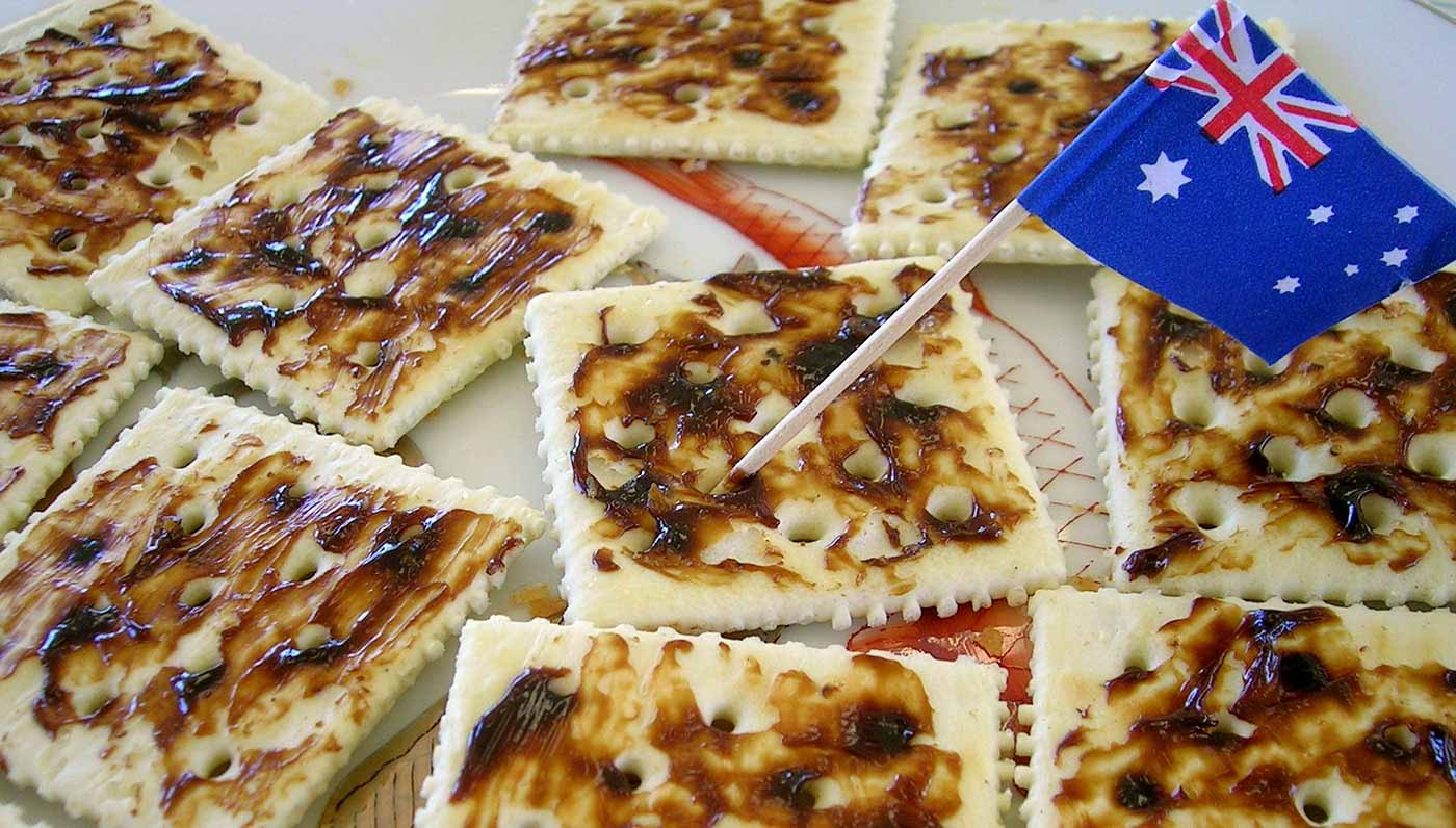 Cracker biscuits spread with Vegemite. One cracker has a toothpick with the Australian flag on it.