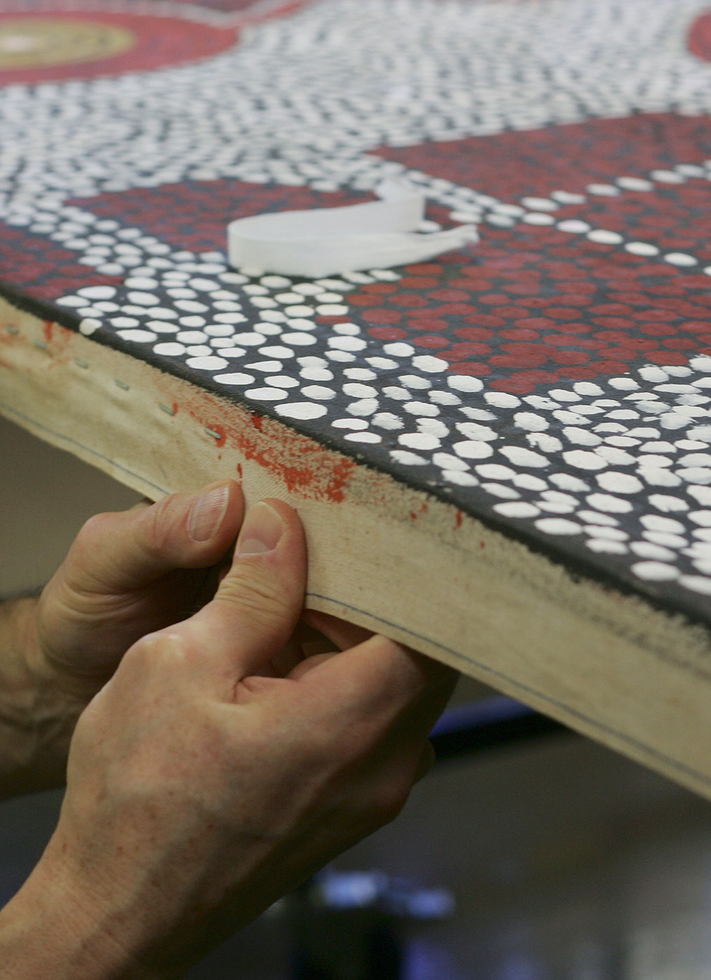 A conservator uses his hands to pull edge of canvas over timber frame. - click to view larger image