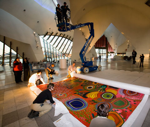 A colour photograph showing museum staff unrolling a large Indigenous painting on the floor of a museum hall. Three of the staff are closest to the camera, while a fourth is at one end of the rolled section of the painting. The visible section of the painting shows a brightly coloured background upon which have been painted numerous traditional patterns and forms. In the background of the photograph, two people watch the unrolling from the bucket of a high-lift crane. Another person is visible filming the unrolling and two others stand in the background with what appears to be camera equipment. One of them has a tripod with what appears to be a camera mounted on top.