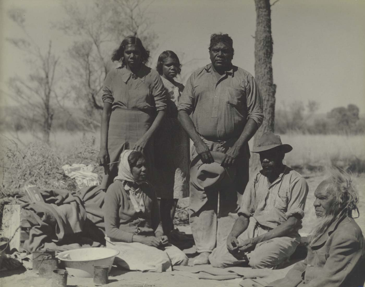 Black and white photo of a group of people sitting and standing in bush land. There are various items around them including tin cans, a basin and blankets.