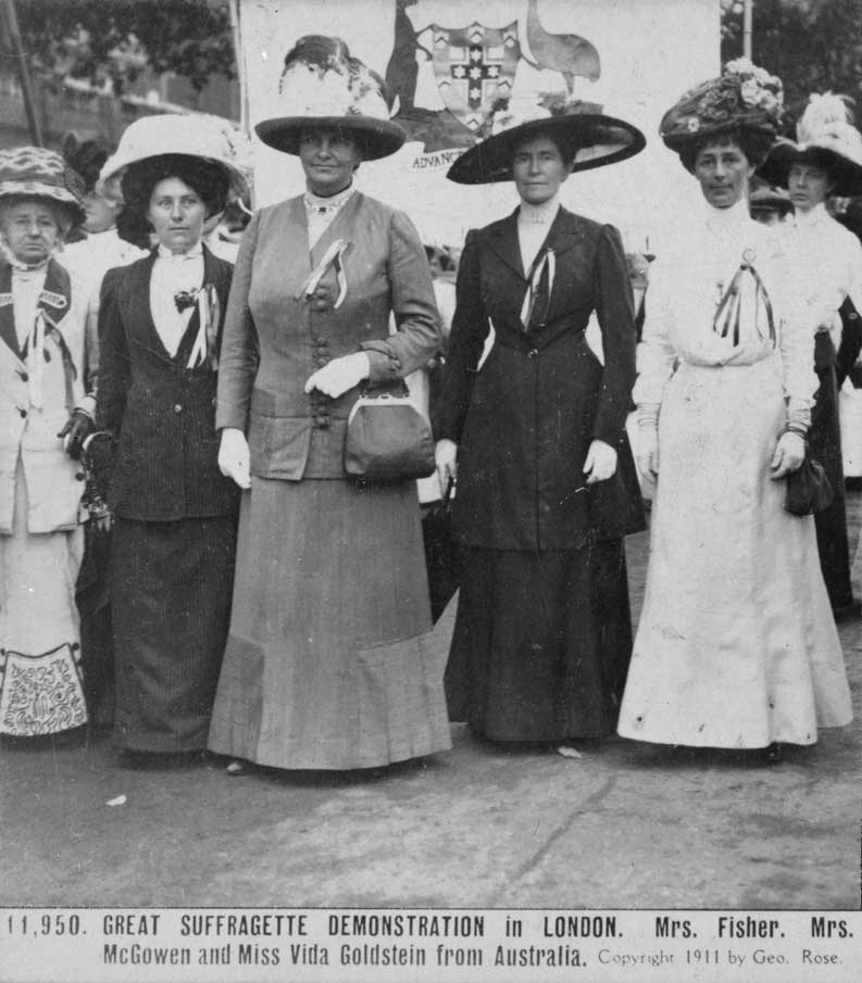 Black and white photograph showing a group of women standing formally in front of a partially visible banner bearing the Australian coat of arms.