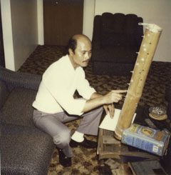 A man sits on a lounge. His right arm points to a bamboo musical instrument, which rests on a small table. The instrument has keys and strings down the side and an olive oil tin at the base.