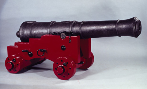 A cannon set on a replica wooden carriage constructed of unknown timbers with metal fittings painted red and black.