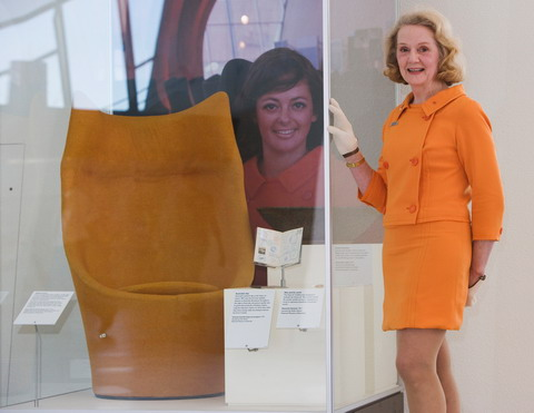 A woman wearing an orange top and skirt stands with her gloved right hand resting on a display case. An orange chair sits in the case, which includes a portrait of another woman at the rear.