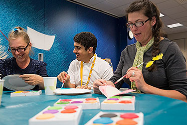 Three people at a table smiling as they paint paper plates