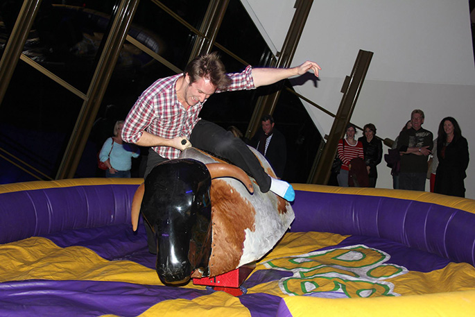 A man riding a mechanical bull.