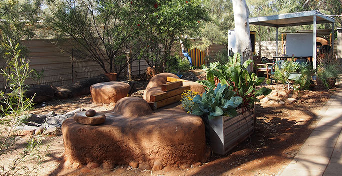 Vegetable garden with fire pit and grinding stone.