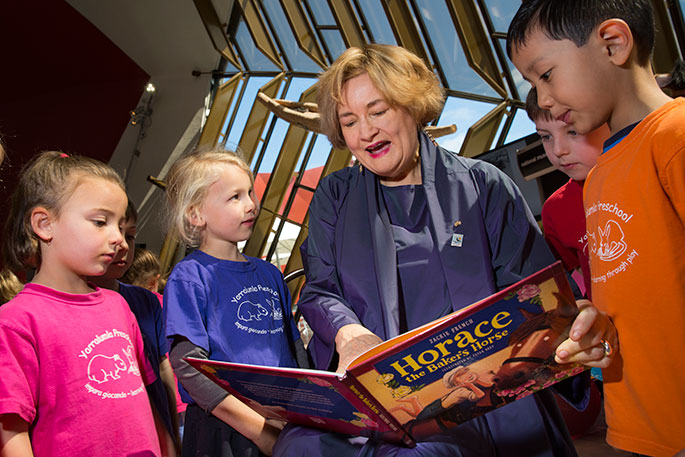 Jackie French holding the book 'Horace the Baker's Horse' surrounded by children