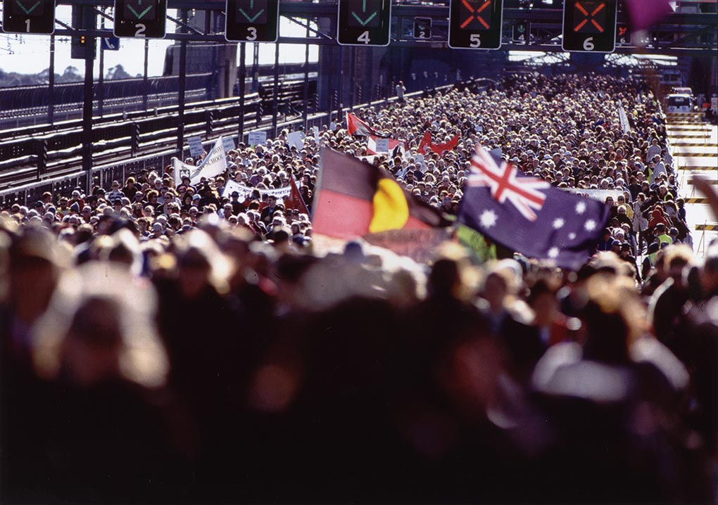 A crowd of hundreds of people walk across a bridge, closed to traffic. People it the foreground carry an Aboriginal and Australian flag.
