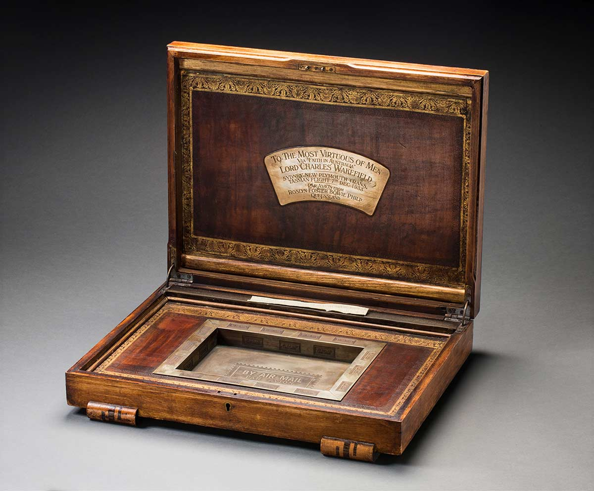 """A wooden box with a raised lid. An engraved metal plaque attached to the underside of the lid, conveys the details: 'TO THE MOST VIRTUOUS OF MEN / VIA """"FAITH IN AUSTRALIA"""" / LORD CHARLES WAKEFIELD / SYDNEY-NEW PLYMOUTH TRANS / TASMAN FLIGHT 7TH DEC 1933 / PAR AVION FROM / ROSLYN FOSTER BOWIE PHILP / QUEENSLAND'. The inscribed date reflects Ulm's changing departure dates."""