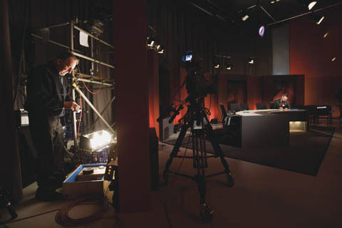 Behind-the-scenes image showing a television set in a studio, with a camera in the centre of the image and a man seated at a semi-circular shaped table at the right. A man stands on the left of the image beside scaffolding, cabling and technical gear.
