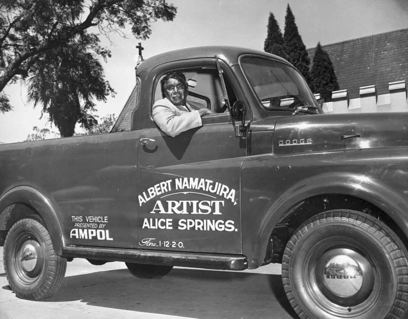 Black and white photo of an Aboriginal man sitting in a truck with 'ALBERT NAMATJIRA ARTIST ALICE SPRINGS' printed on the outside. - click to view larger image