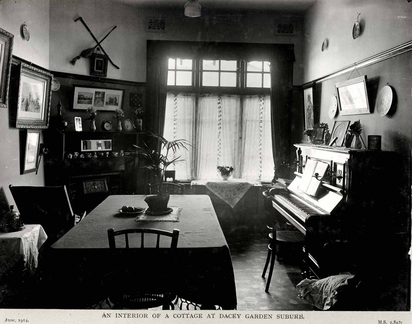Black and white photograph showing part of a dining room, with a table at centre and piano at right.