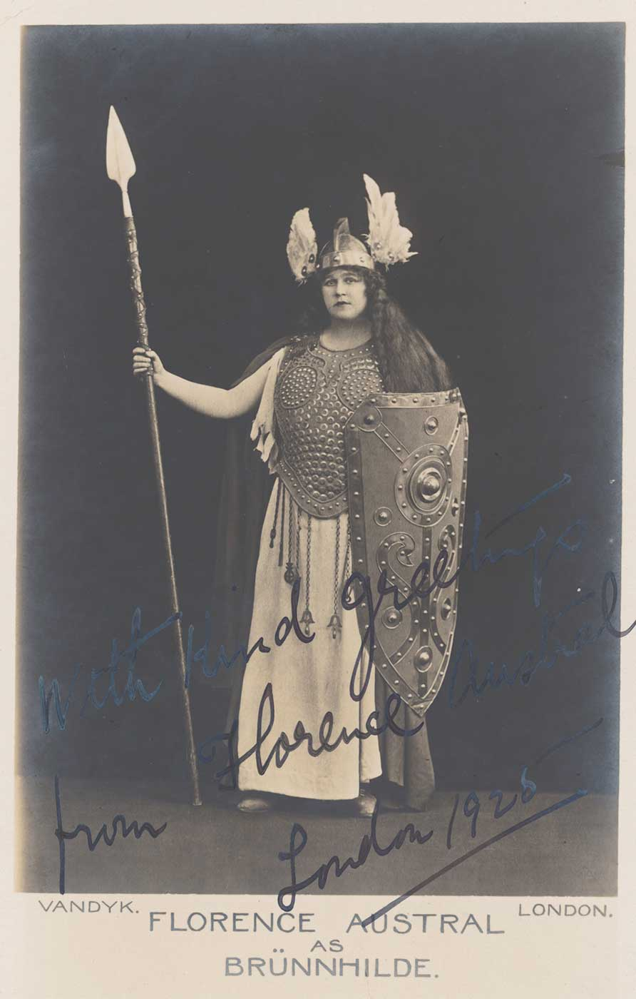 Studio portrait of Florence Austral wearing a two-pronged helmet and carrying a spear and shield, in costume as Brunnhilde.