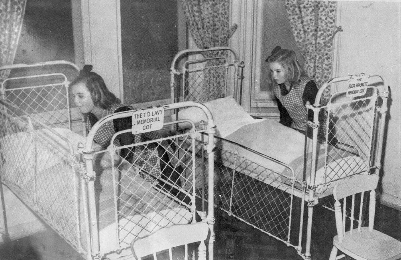 Black and white image showing two young girls tucking in bedding on metal and wire baby cots. The girls wear checked smocks over dark tops and have ribbons in their hair. The cot on the left has a metal plaque at the end which reads 'THE TD LAVY MEMORIAL COT'. - click to view larger image