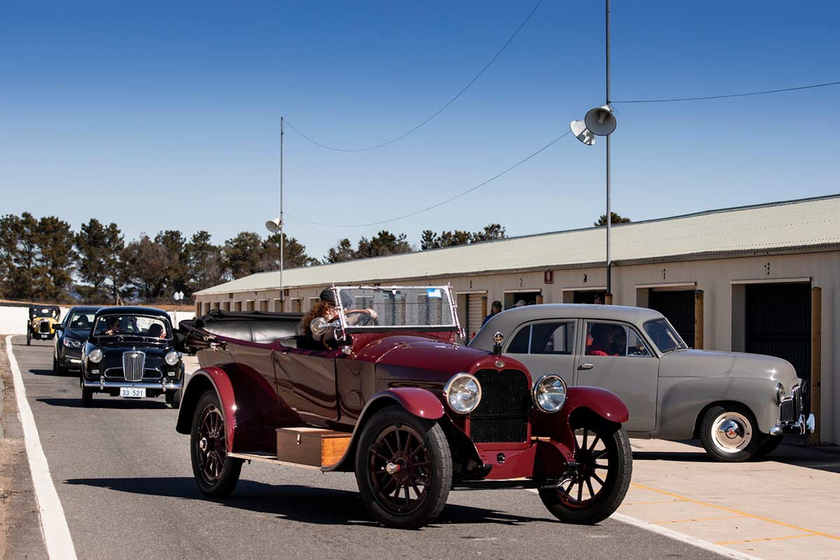 Vintage cars on display at a raceway track. - click to view larger image