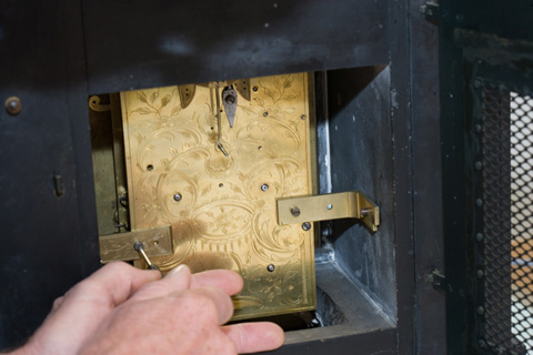 Brass brackets secure the movement to the internal walls of the case.