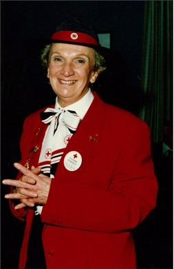 Portrait showing a woman wearing a red jacket and a black hat with red band and pin. The woman is smiling and wears several Red Cross badges and pins.