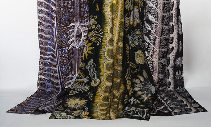 Silk batik fabric with Ernabella motifs in yellow, black, blue and white.