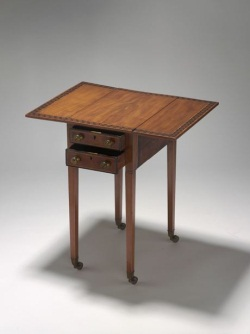 Rectangular wooden table, with fold-down side leaves. The table features narrow inlaid ivory borders, including a wide inlaid border of contrasting timber in a geometric pattern on the table top. The table has four square tapering wooden legs, each terminating in a brass cup and castor. The table has two drawers, each with two round metal knob handles and a brass key-operated lock.