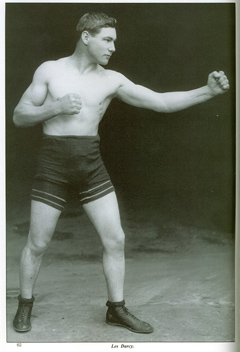 Side view of Les Darcy in shorts and boots. His fists are closed and he is leading with the left.
