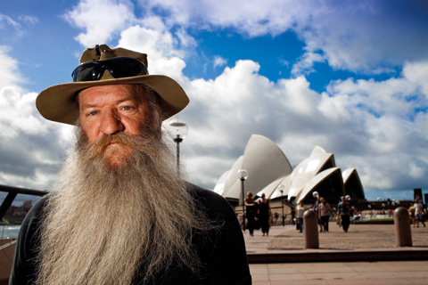 Portrait of a man with a long grey beard, and wearing a khaki hat with sunglasses on top, standing to the left, with a distant view of the Sydney Opera House, people walking on a concourse, and a blue sky with white clouds.