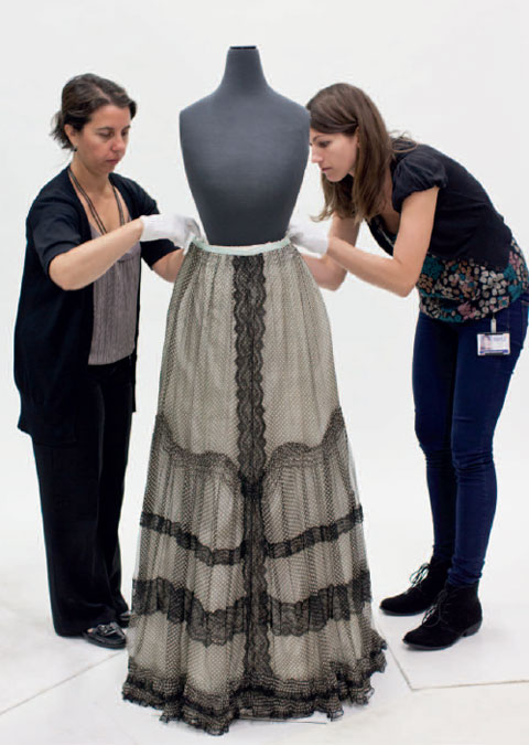 Two women stand either side and slightly to the rear of a mannequin. The mannequin's torso has neither arms nor a head and is finished in a dark grey material. The women, both wearing short white gloves, lean in to adjust the waistband of a skirt, which covers the lower half of the mannequin. The long skirt is mainly light grey in colour, with black lace down the centre, around the hem and in three vertical bands from about knee to hem.