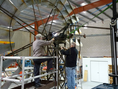 Rear view of two men working at height, on a windmill. One man is applying heat gun to a piece of metal.