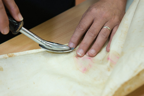 A small heated spatula is used to heat-set the adhesive securing the silk backing over the weak area. Silicone-release film separates the silk garment from the heated spatula.