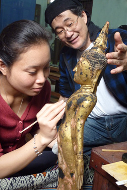 A woman leans in to apply a fine brush to a small gold sculpture. A man observes her work and supports the rear of the statue's head.