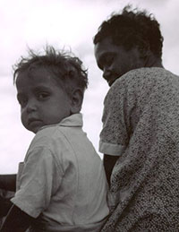 Black and white photo of a young boy with his mother.