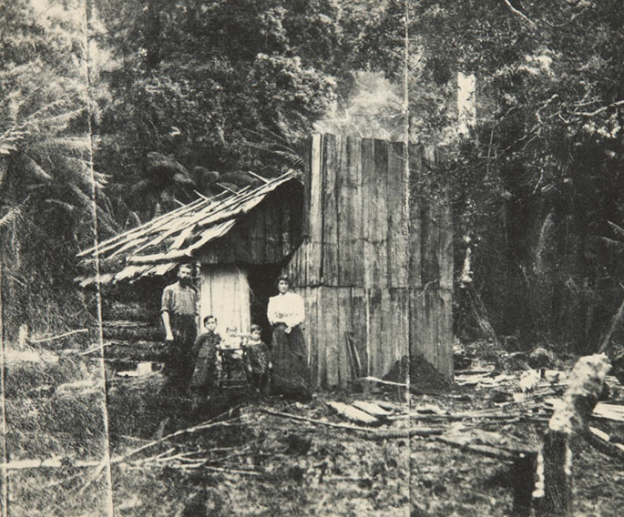 Family shot posing outside a timber hut with smoke rising from the chimney and logs lying on the ground.