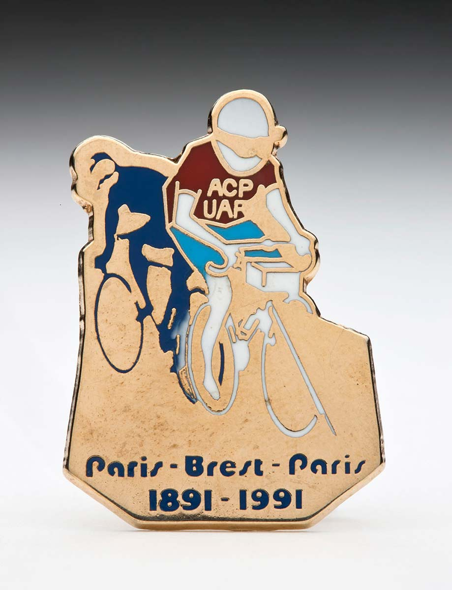 Gold badge with two cyclists at top and Paris-Brest_Paris 1891-1991 at bottom. - click to view larger image