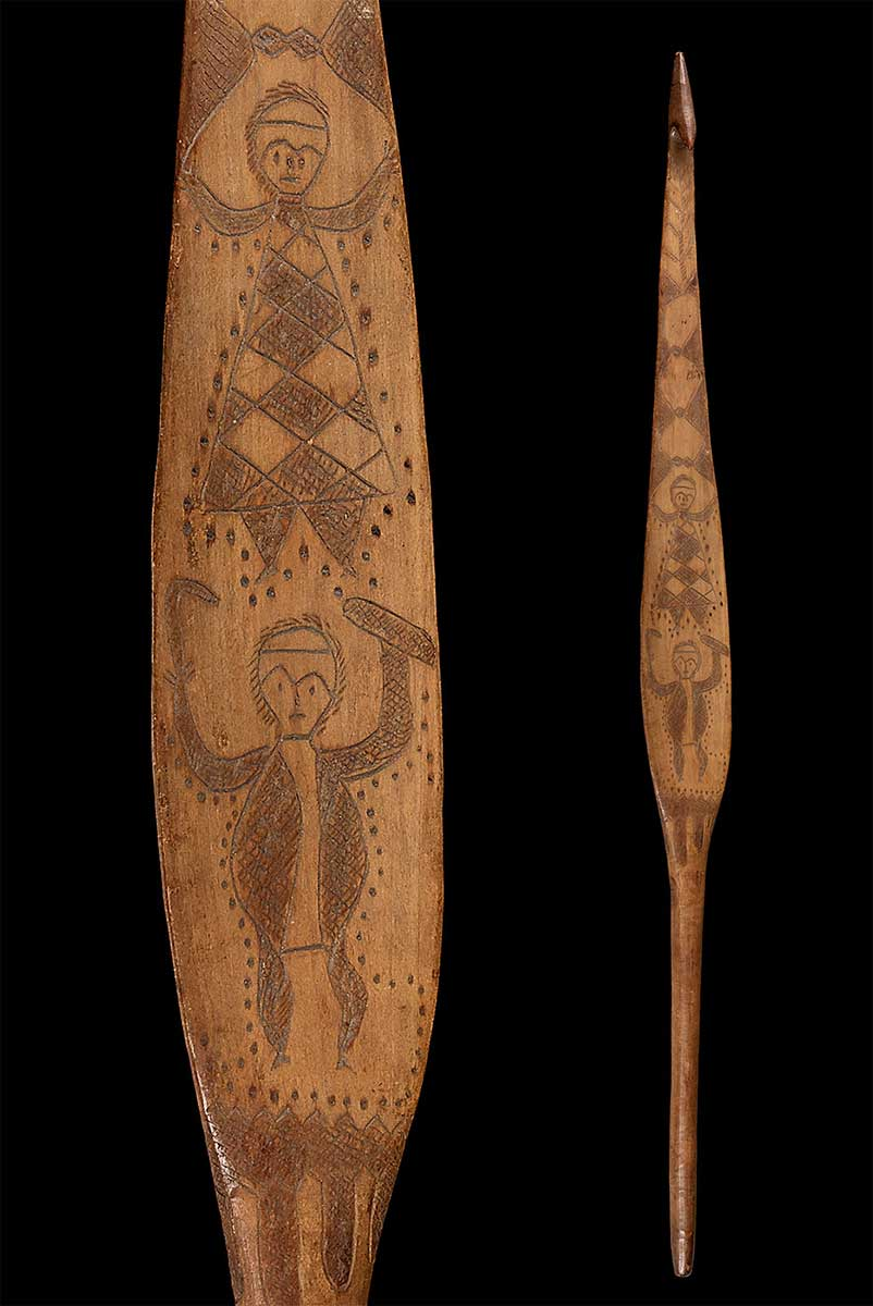 Spear-thrower made of wood, decorated with complex incised figurative designs, including two human figures; one holding a shield and a boomerang, the other clothed in a decorated skin cloak. - click to view larger image
