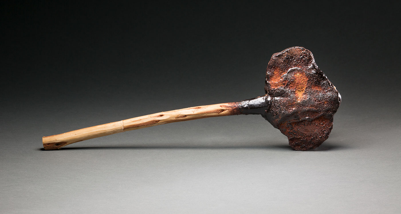 A 'Kodj' axe with a stone head and a wooden handle. The handle is connected to the head with dark coloured resin. The head of the axe has a rust coloured substance on it which may be part of the resin.