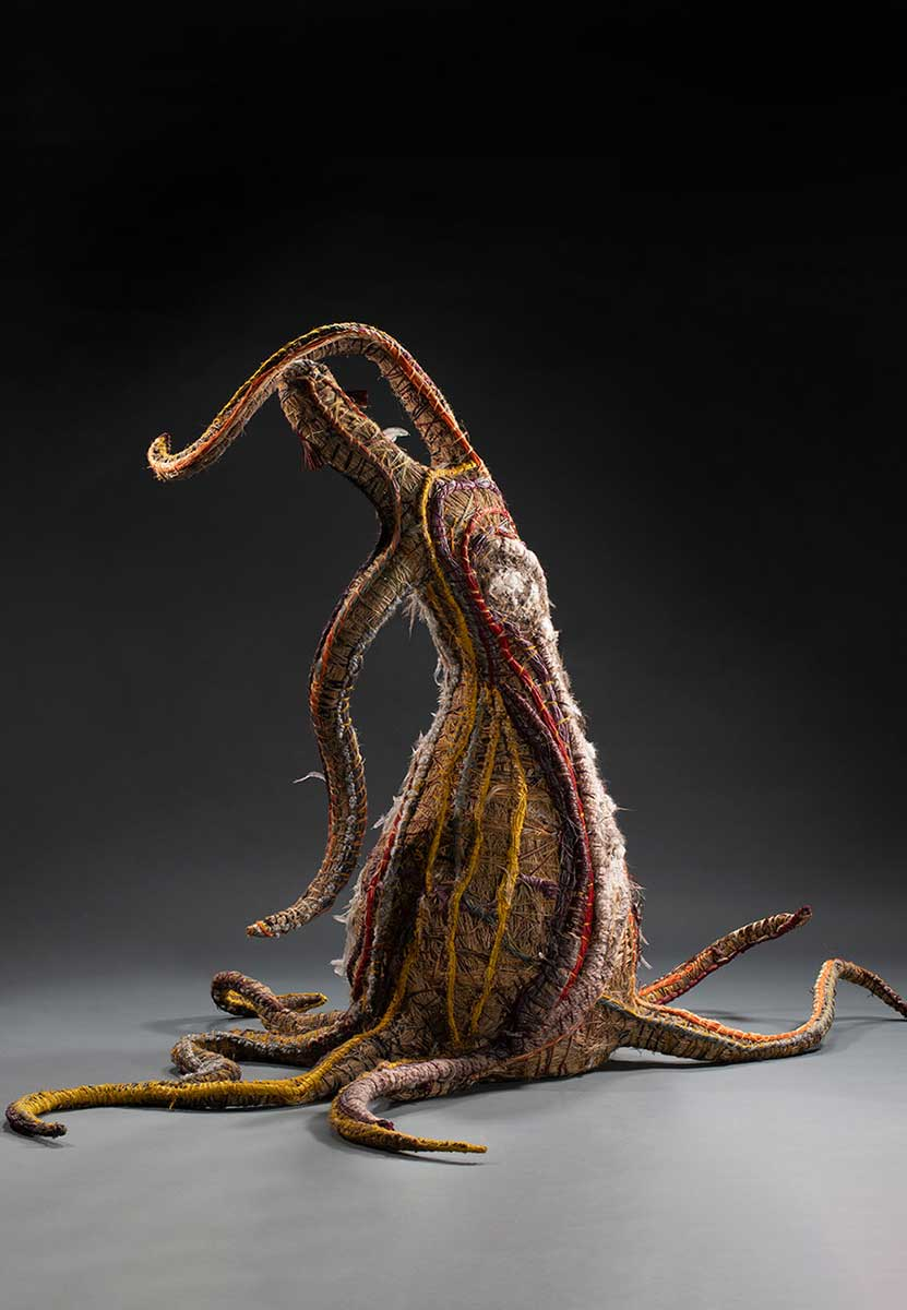 A tree sculpture baring human like features. The sculpture is made of various plant and synthetic materials. - click to view larger image