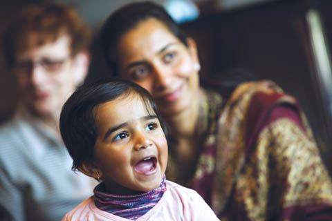 A young girl, singing, is in focus at the centre of the shot, with her mother, smiling, and slightly out of focus in the background.