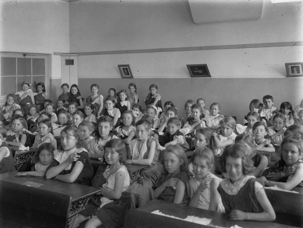 Black and white photograph showing a classroom of young girls, seated at desks. Many are lifting their left sleeve so show their upper arm.