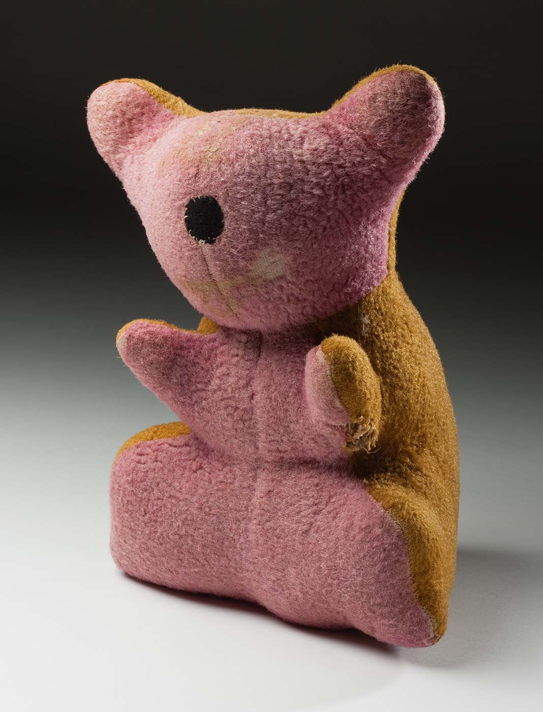 A small bear shaped like a koala, with pink plush fabric on the front and a mustard coloured plush on the back. It has a circular black felt nose with white hand stitching. The bear's left arm and part of its face are worn. - click to view larger image