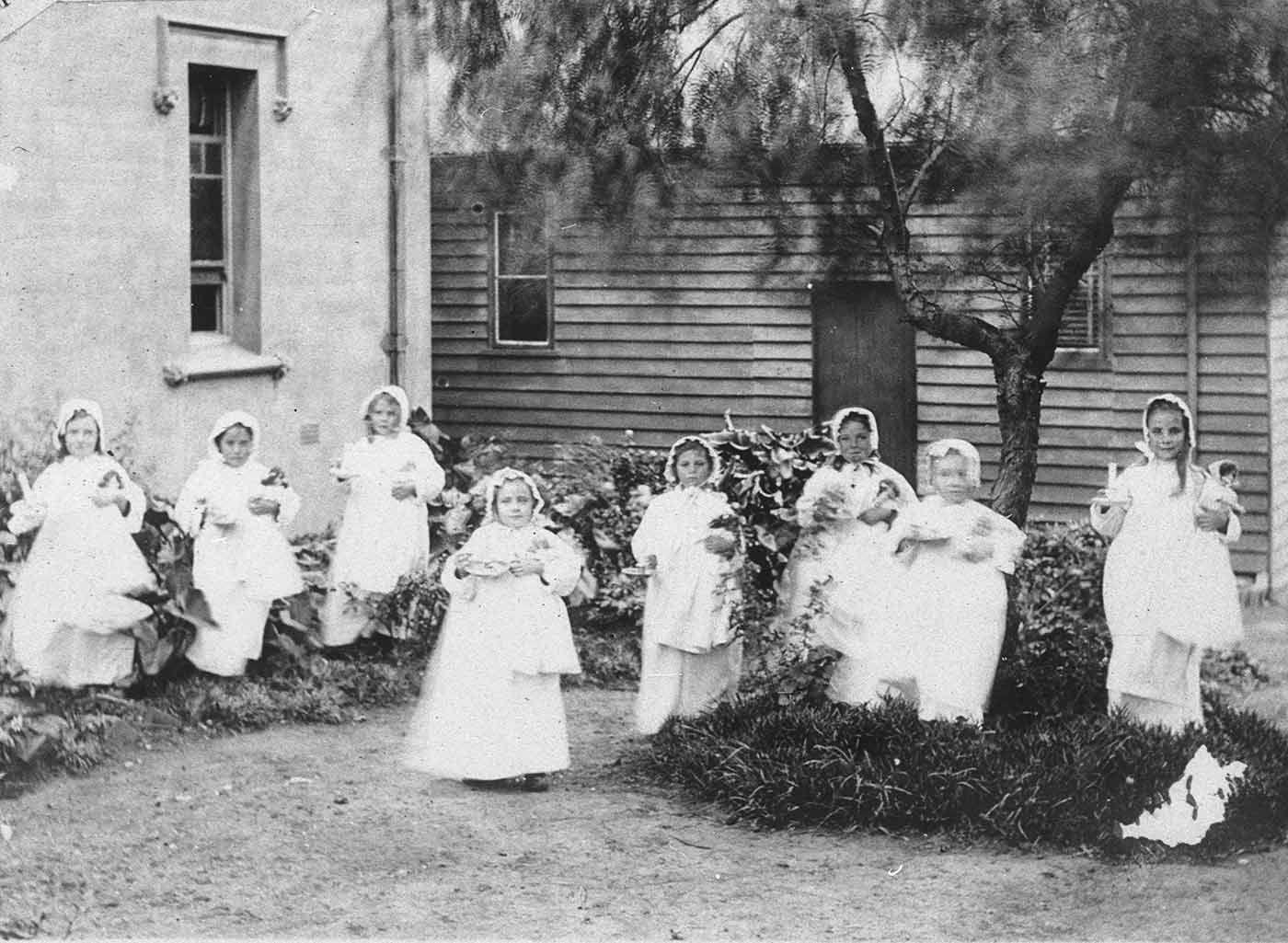 Black and white photo of a group of young girls. The girls are standing in a garden with some under a tree. Two buildings can be seen in the background.  Each of the girls is wearing a long dress and bonnet and is holding a doll in their left arm and a candle in their right hand. - click to view larger image