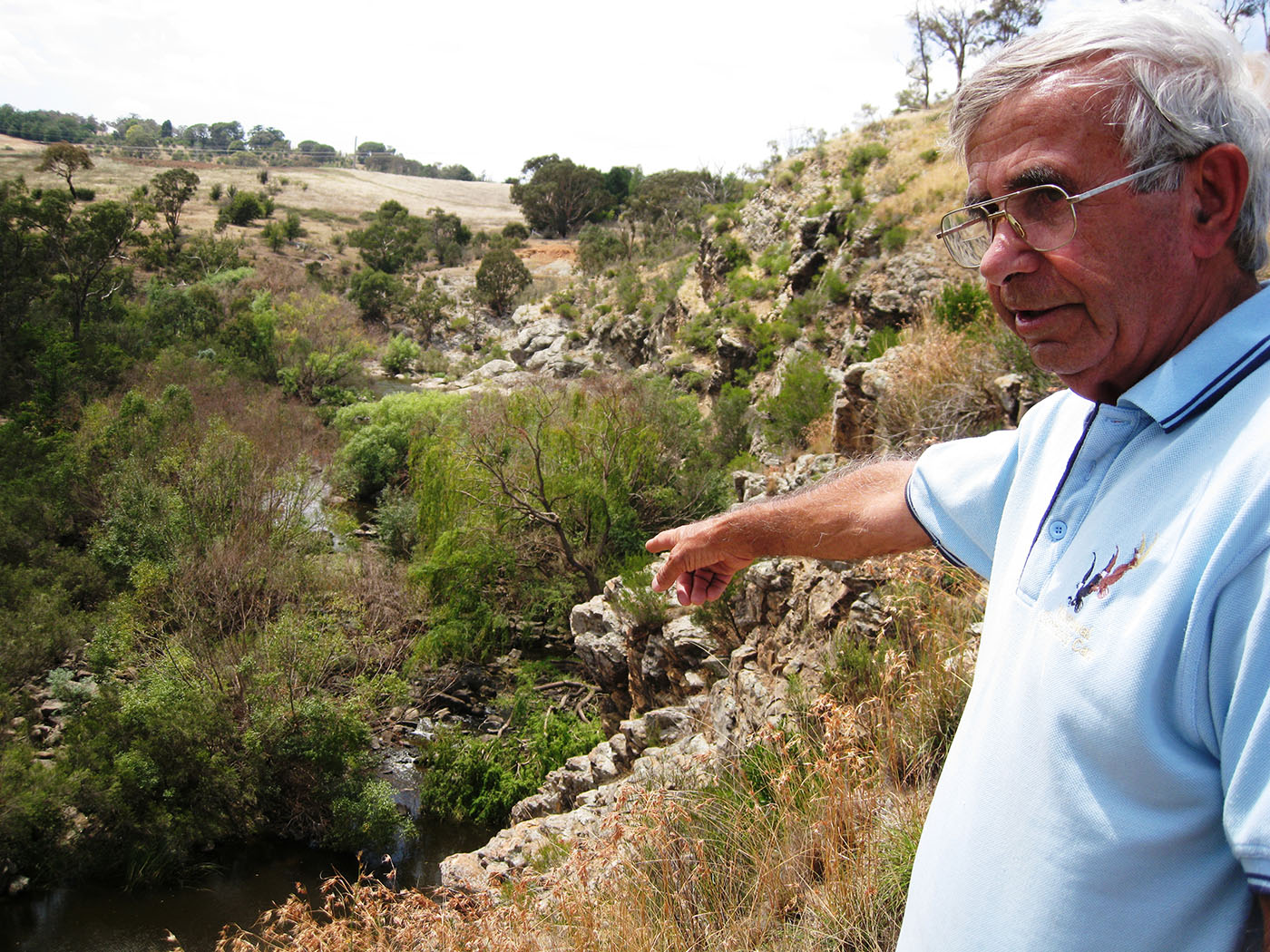 Eric Bell stands on a hillside, pointing to a small river below.