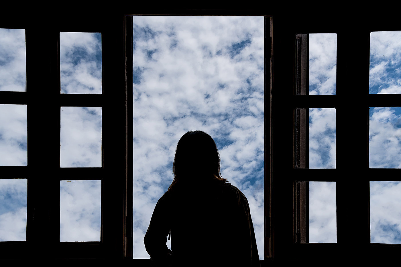 Silhouette of a person looking out of a window with a blue sky beyond. - click to view larger image