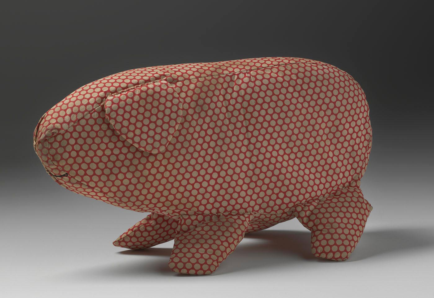 A soft toy in the shape of a pig made from off-white spotted red cotton fabric. The pig has a triangular ear and is missing its tail. A curved mouth is sewn onto the fabric in black thread. - click to view larger image