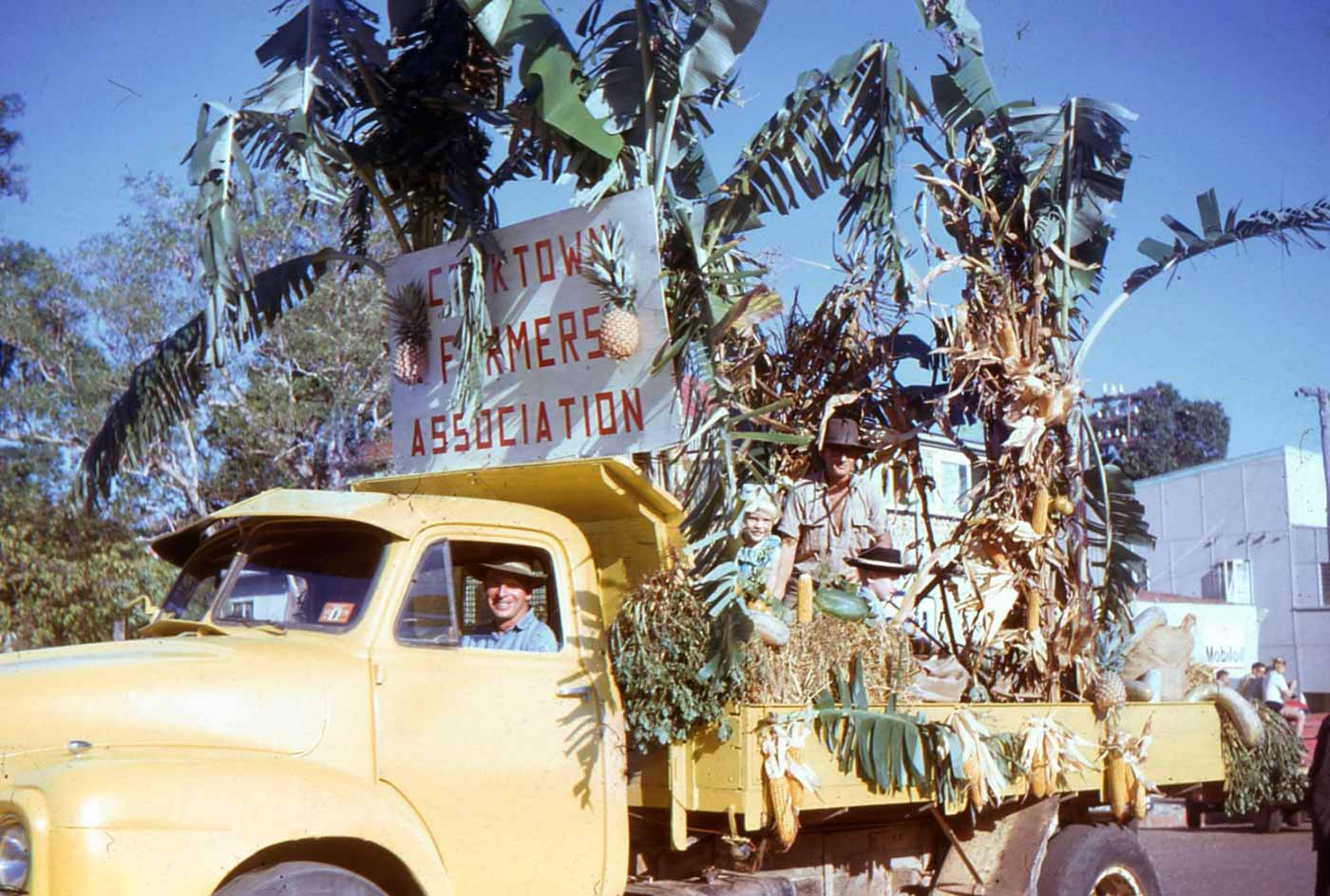 Colour photo of a yellow truck transformed into a parade float carrying people sitting amongst palms and hay bales. There is a sign that reads 'COOKTOWN FARMERS ASSOCIATION'. - click to view larger image
