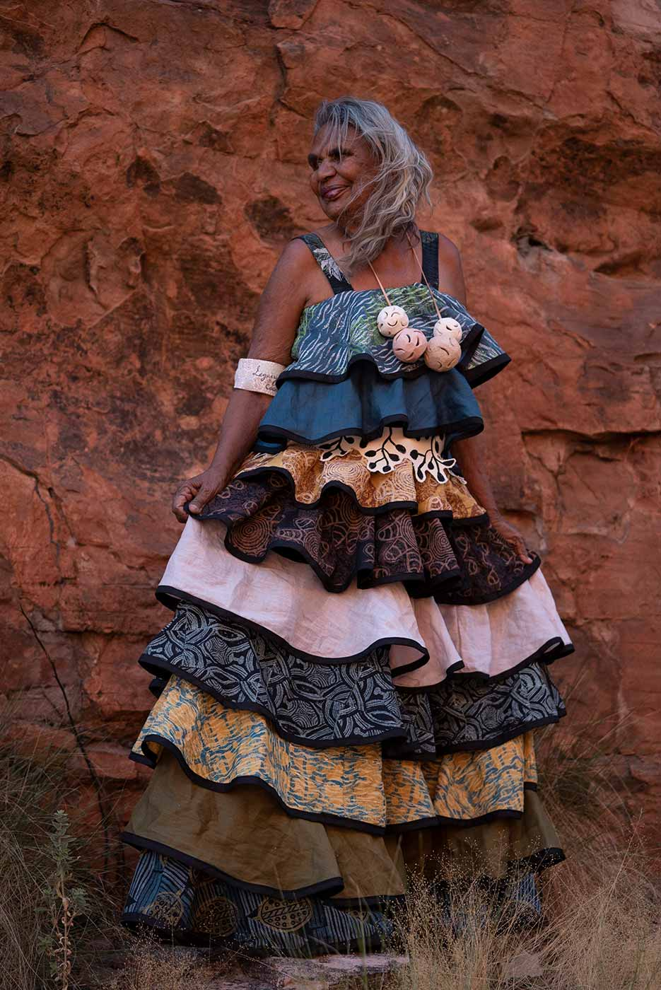 Woman standing in front of a red rockface wearing a layered ruffled dress of different colours - click to view larger image