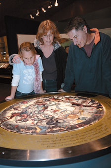 Visitors Cassie, Julie and Martyn Toole examining the 'Encounters' map in the Horizons gallery.